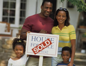 Family with a sold sign on their new house