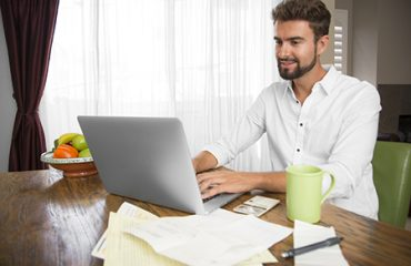 Man smiling at laptop while completing his taxes.